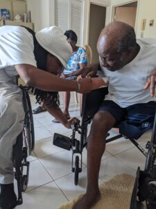 Two men in wheelchairs looking down at a part of the wheelchair. The man on the left is adjusting the wheelchair's footrest of the man on the right.