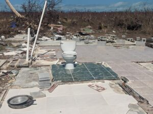 A home totally flattened by Hurricane Dorian, leaving only a toilet remaining, and debris scattered around.