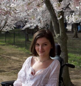 Anna Landre, a white-passing woman with chin-length brown hair, smiles at the camera while posing in her wheelchair.