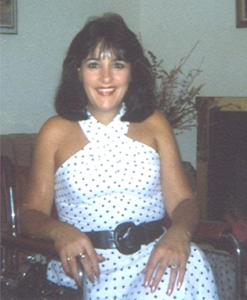Photo of Benny, smiling, long black hair, wearing white dress with black polka dot dress, seated in her wheelchair.