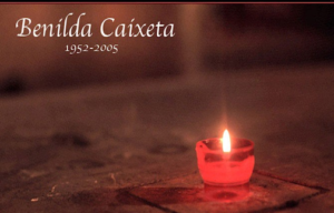 """Picture of a small candle. The text above the candle reads """"Benilda Caixeta"""" and """"1951-2005."""""""